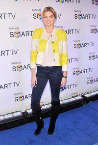 Model Kate Upton lyk hip en smart in stewels en broek.