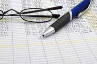 `N close-up van `n bril en `n inkpen op `n rekeningkundige grootboek.