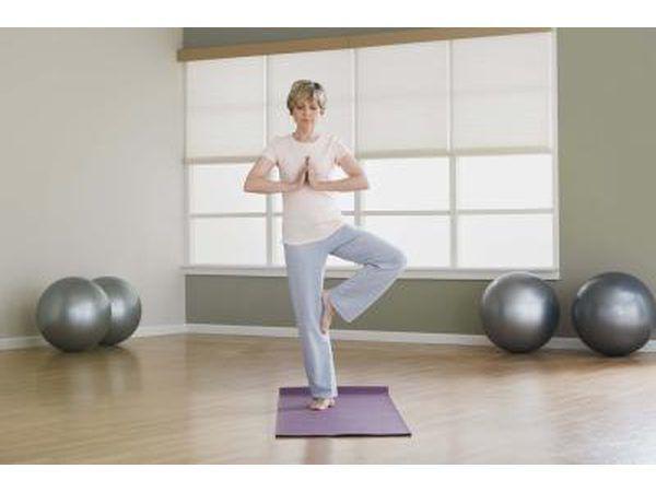 `N Vrou`s op een voet in `n joga inhou.