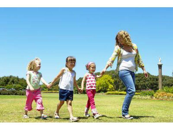 A nanny neem drie meisies om die park.