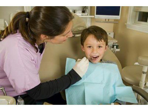 A tandheelkundige hygenist ondersoek `n kind`s teeth.
