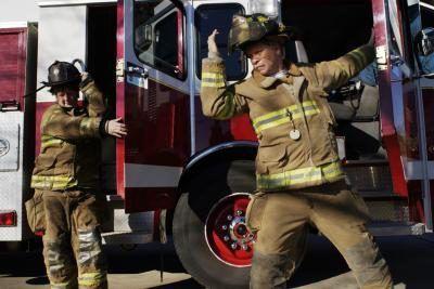Twee vroulike brandbestryders verlaat `n brandweerwa.