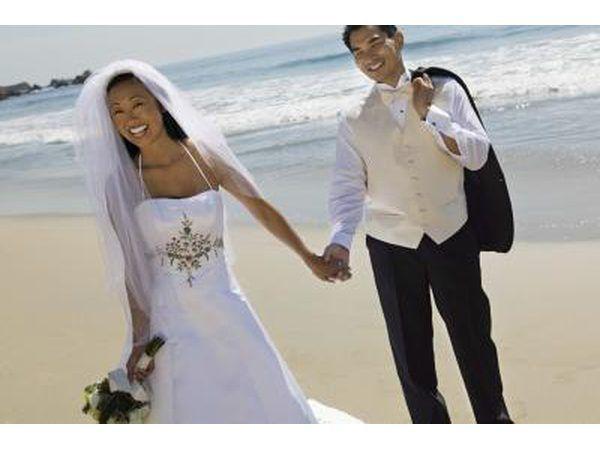 Bruid en bruidegom hou hande op die see