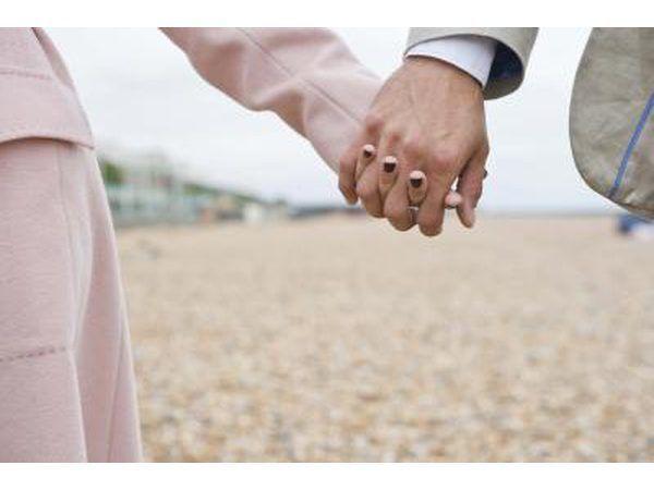 Egpaar hande vashou op die strand