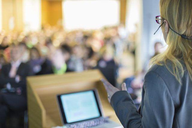 Vroulike spreker agter `n podium te gee `n aanbieding